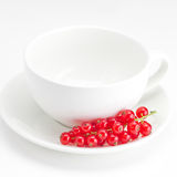 Currants and a cup with a plate isolated on white Royalty Free Stock Photos