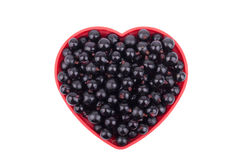 Currants in a dish in the shape of a heart. Royalty Free Stock Image