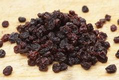 Currants in a pile. A pile of dried currants on a wooden chopping board Royalty Free Stock Photo