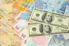 Currencies. World finance and foreign currency exchange concept - money background with US dollars, Swiss franks, Polish zloty, Euros and Malaysian ringgit