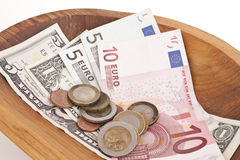 Currencies. Money in a wood bowl Stock Photography