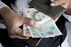 Currency. Putting currency notes in purse Stock Images