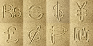Currency abbreviations Written in the Sand. Golden colors Royalty Free Stock Images