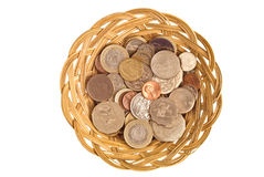 Currency Basket. Mixed international coins in a simple cane basket. Concepts of currency exchange, globalism, globalisation, international trade especially third Royalty Free Stock Image