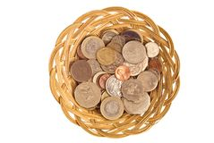 Currency Basket Mixed International. Mixed international coins in a simple cane basket. Concepts of currency exchange, globalism, globalisation, international Royalty Free Stock Image