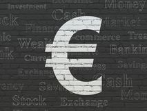 Currency concept: Euro on wall background. Currency concept: Painted white Euro icon on Black Brick wall background with  Tag Cloud Stock Image