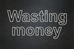 Currency concept: Wasting Money on chalkboard background. Currency concept: text Wasting Money on Black chalkboard background Royalty Free Stock Images