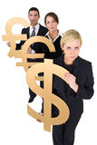 Currency Concerns. A team of three young executives, one man and two women, holding currency symbols and looking worried stock photo