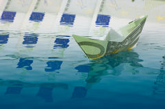Currency crisis. Paper ship made of euro banknote sailing on money Royalty Free Stock Image
