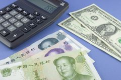 Currency exchange. US and Chinese currency with calculator depicting currency exchange Royalty Free Stock Photos