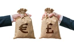 Currency exchange concept. Hands holds bags full of money - British pounds and Euro Royalty Free Stock Photography