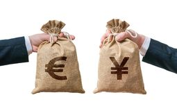 Currency exchange concept. Hands holds bags full of money - Euro and Yen Stock Photo