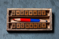 Currency exchange concept. Vintage box, wooden cubes phrase with old style letters, red blue pencil. Gray stone textured. Background. Close-up, up view, soft Royalty Free Stock Image