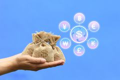Currency exchange rate for investment and business concept, Woman hand holding coins money in bag with hologram on blue background royalty free stock photos