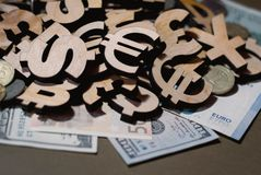 Currency icons and real money lie on the desk stock image