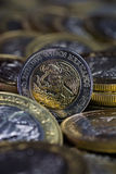 Currency of a Mexican peso between more coins Royalty Free Stock Photo