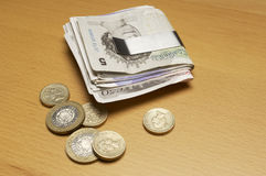 Currency In Money Clip And Coins On Table stock images