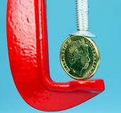Currency Pressure. A gold coin held in a red clamp with a light pastel green background, indicating the pressure is on currency during these uncertain times Stock Photo