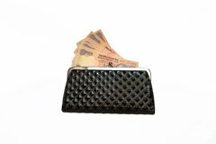 Currency in Purse. A black purse containing Indian currency notes isolated on white background Stock Image
