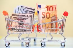 Currency rate concept. Euro and dollar currency in shopping carts opposite each other Royalty Free Stock Photography