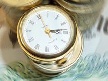 Currency in a spin. Money conceptual image showing watch on UK currency with added spin effect stock photo