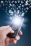 Currency symbols fly from a mobile phone Stock Photography