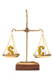 Currency value dollar and euro. Dollar and euro pound symbols balanced on weighing scales Stock Photo