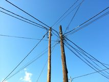 Tangle of electric cables, with blue sky. Current, electric, electricity, electric, electric, power, mess, tangle, disorder, wood, turret, tower, light Stock Images