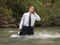Current job. Man in business attire and briefecase standing mid-stream in a river on his cell phone Royalty Free Stock Images