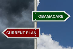 Current Plan versus Obamacare. Red and green street signs with blue and stormy sky with words Current Plan and Obamacare Stock Image
