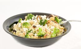 Curried couscous. Combine couscous, broccoli, shredded carrots, raisins, nuts, garbanzo beans, and seasonings top with feta cheese and serve hot or cold Royalty Free Stock Images