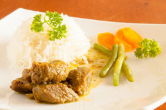 Curried Goat served with white rice, string beans and sliced carrots Stock Photo