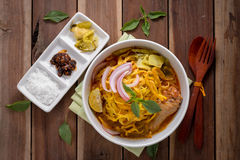 Curried Noodle Soup (Khao soi) with coconut milk on wooden table Royalty Free Stock Image