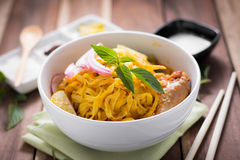 Curried Noodle Soup (Khao soi) with coconut milk on wooden table Stock Image