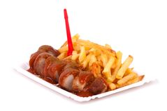 Curried sausage and chips. A bowl with curried sausage and chips in front of white background Stock Photos