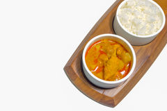 Curry chicken with jasmin rice. Isolate of a curry chicken with jasmin rice on nature wooden plate, on top view and white background Stock Photos