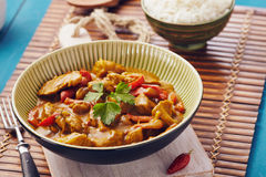 Curry chopped pork. In a bowl with basmati rice on a bamboo placemat on a blue wooden table Royalty Free Stock Image