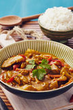 Curry chopped pork. In a bowl with basmati rice on a bamboo placemat on a blue wooden table Stock Photos