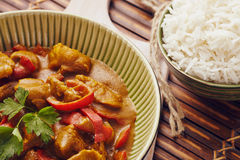 Curry chopped pork. In a bowl with basmati rice on a bamboo placemat on a blue wooden table Royalty Free Stock Photo