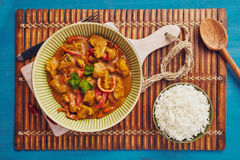 Curry chopped pork. In a bowl with basmati rice on a bamboo placemat on a blue wooden table Stock Photography