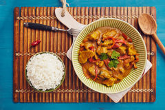 Curry chopped pork. In a bowl with basmati rice on a bamboo placemat on a blue wooden table Royalty Free Stock Photos