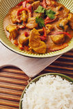 Curry chopped pork. In a bowl with basmati rice on a bamboo placemat on a blue wooden table Stock Image