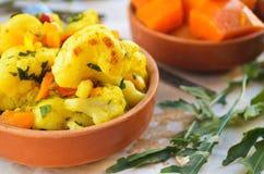 Curry de la coliflor con la calabaza, la paprika y el arugula Foto de archivo libre de regalías