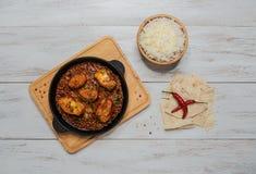 Curry de los pescados del bengalí y fijar las especias indias con el arroz basmati en la tabla de madera imagenes de archivo