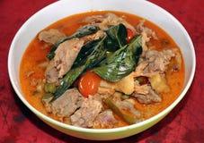 Curry del pollo con la bacca del basilico, del pomodoro e del tacchino nella ciotola sulla tavola di legno rossa fotografie stock libere da diritti