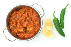 Curry dish. Hot chicken jalfrezi in a curry dish with lemon wedges and green chili peppers on the sdie, over a white background royalty free stock image