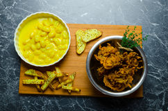 Curry gnocchi with bhajjis and roasted potato. On wood plate stock images