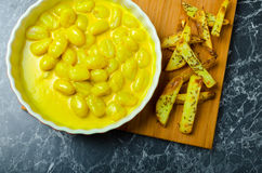 Curry gnocchi with bhajjis and roasted potato. On wood plate stock photo
