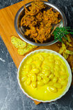 Curry gnocchi with bhajjis and roasted potato. On wood plate stock photos