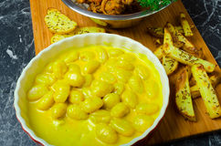 Curry gnocchi with bhajjis and roasted potato. On wood plate royalty free stock photography